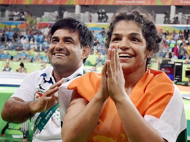 India's Sakshi Malik with her coach Kuldeep Singh, celebrate after winning bronze against Kyrgyzstan's Aisuluu Tynybekova in the women's wrestling freestyle 58-kg competition, at the 2016 Summer Olympics in Rio de Janeiro, Brazil on Wednesday. PTI Photo by Atul Yadav  (PTI8_18_2016_000075B)