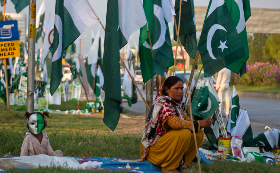 A Pakistani vendor waits for customers with her daughter to sell national flags, badges and masks ahead of Pakistan Independence Day in Islamabad on Friday. Pakistani will celebrate its 70th Independence Day on 14 August, 2016. AP