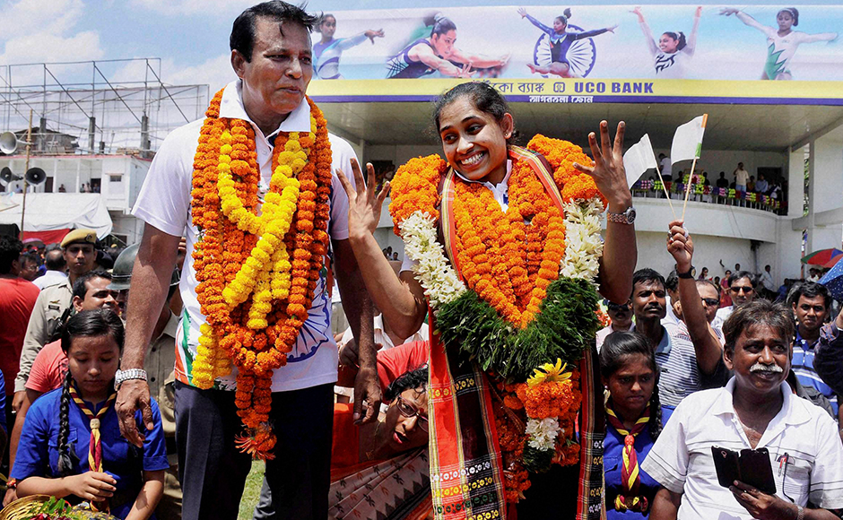 Gymnast Dipa Karmakar and her coach BS Nandi being accorded warm welcome upon their arrival at the airport in Agartala.PTI