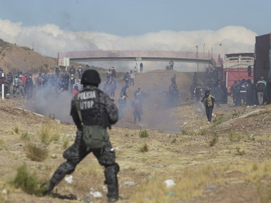 "Independent miners clash with the police as they run from clouds of tear gas during protests in Panduro, Bolivia, Thursday, Aug. 25, 2016. Government officials said that the striking miners kidnapped and beat to death the country's deputy interior minister after he traveled to the area to mediate in the bitter conflict over mining laws. Government Minister Carlos Romero called it a ""cowardly and brutal killing"" and asked that the miners turn over the body of his deputy, Rodolfo Illanes. AP"