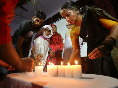 People lighting candles at the Amnesty International India's event. AP