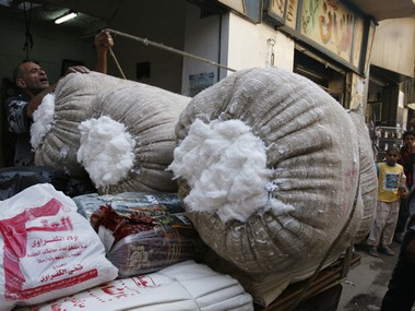 An Egyptian tradesman prepares to move a sack full of cotton to a car for sale at a market in Cairo