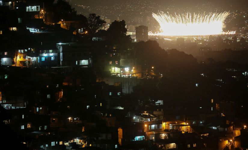 Fireworks explode over Maracana stadium with the Prazeres 'favela' community in the foreground during opening ceremonies. Getty