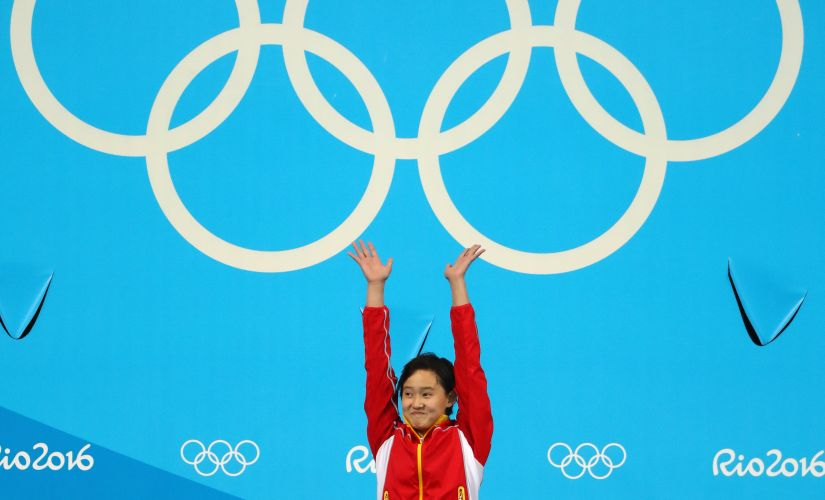 Gold medalist Qian Ren celebrates on the podium during the medal ceremony. Getty