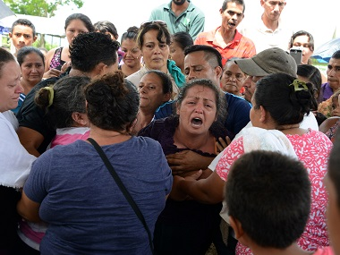 Honduran Olga Lopez (C) cries during the funeral of her daughter Jennifer, 10. AFP