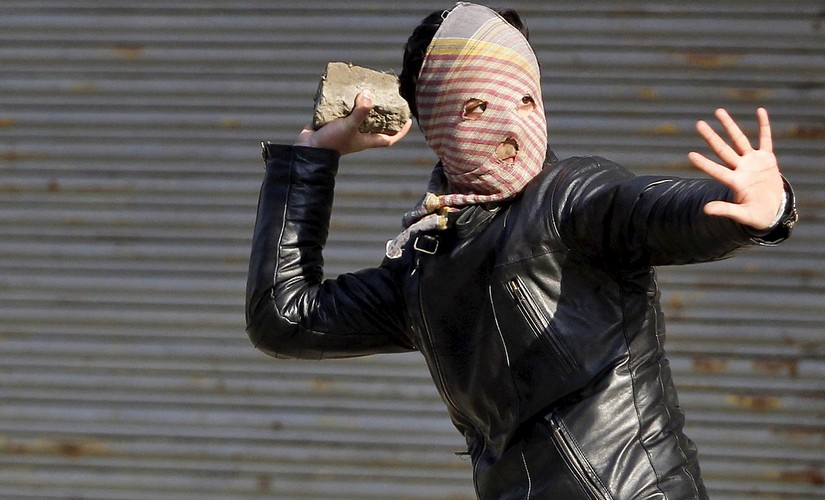 A protestor throws a stone towards Indian security forces in Kashmir. Reuters