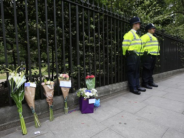 Floral tributes rest against railings near the scene of the fatal stabbing in London. PA via AP