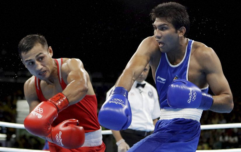 Fazliddin Gaibnazarov and Manoj Kumar exchange punches during a men's lightwelter weight 64-kg preliminary boxing match. AP