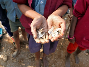 A girl shows some of the mica flakes she has collected whilst working in a open cast illegal mine in Giridih district in Jharkhand. Reuters