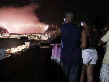 2016 Rio Olympics - Opening ceremony - Maracana - Rio de Janeiro, Brazil - 05/08/2016. A family photograph fireworks over the Maracana stadium from the roof of their home in the Mangueira favela, or slum, as the Olympic opening ceremony unfolds. REUTERS/Ricardo Moraes - RTSLBD0