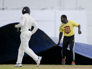 The ground staff at Queens Park Oval bring the covers out as Rohit Sharma (left) jogs out of the ground. AP