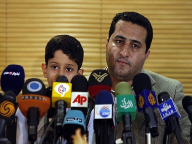 FILE--In this file photo taken on Thursday, July 15, 2010, Shahram Amiri, an Iranian nuclear scientist attends a news briefing while holding his son Amir Hossein as he arrives at the Imam Khomeini airport just outside Tehran, Iran, after returning from the United States. Amiri, who was caught up in a real-life U.S. spy mystery and later returned to his homeland and disappeared, has reportedly been executed under similarly mysterious circumstances. Amiri was reportedly hanged this week and family members held a memorial service for him in the Iranian city of in Kermanshah, 500 kilometers (310 miles) southwest of Tehran. State media in Iran, which has been silent about Amiri's case for years, has not reported his death.  (AP Photo/Vahid Salemi, File)