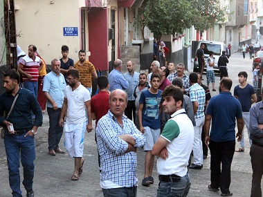 "People gather to view damage just hours after Saturday's bomb attack in Gaziantep, southeastern Turkey, early Sunday, Aug. 21, 2016, targeting an outdoor wedding party in southeastern Turkey killed dozens of people and wounded dozens. Deputy Prime Minister Mehmet Simsek said the ""barbaric"" attack in Gaziantep, near the border with Syria, on Saturday appeared to be a suicide bombing. Turkish authorities have put a temporary ban on distribution of images relating to Saturday's Gaziantep attack within Turkey. (IHA via AP)"