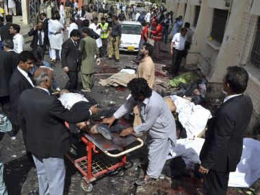 People help victims of a bomb blast in Quetta, Pakistan on Monday. PTI