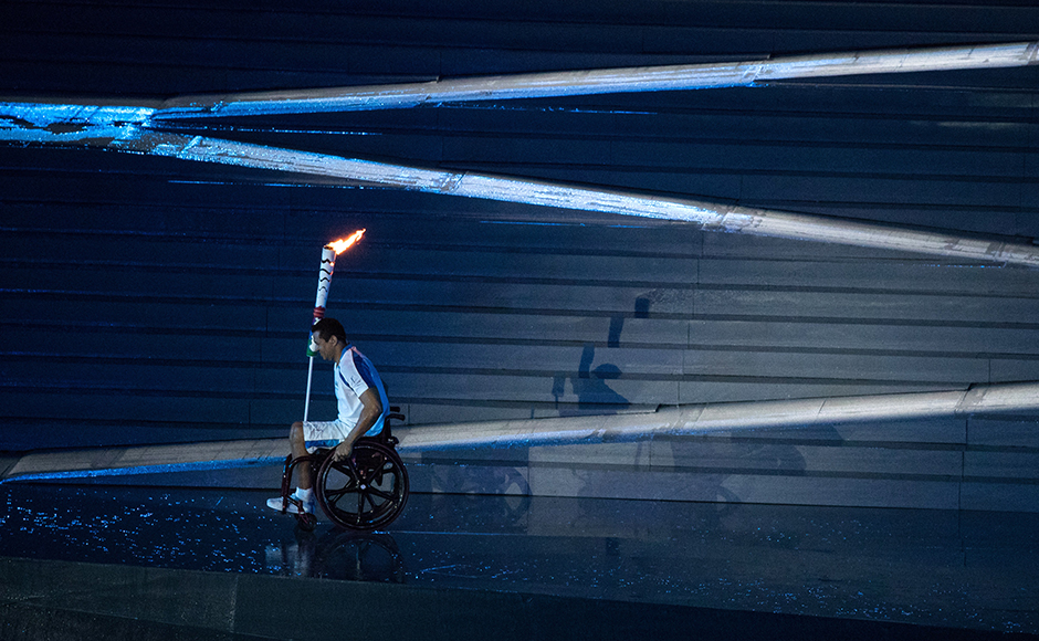 Brazilian Paralympic swimmer Clodoaldo Silva carries the torch during the opening ceremony. Reuters