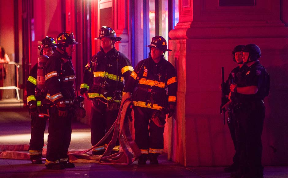 """Firefighters gather as heavily armed police block the area while they search for an explosive device on West 27th street and 7th Avenue in Manhattan, New York. An explosion in a crowded Chelsea neighborhood in Manhattan on Saturday night left more than two dozen people injured, and authorities called the blast an """"intentional act,"""" but said there was no terrorist connection. New York Mayor Bill de Blasio also said a second site on 27th Street was being investigated. AP"""