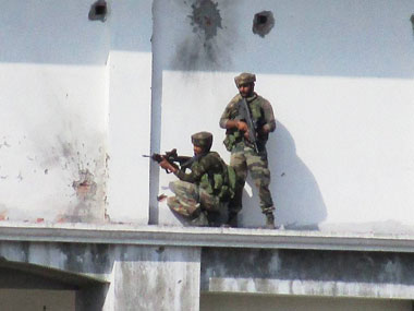 Security personnel take positions near the building where terrorists were hiding during the 3nd day of encounter at Allah Pir area in Poonch on Tuesday. PTI