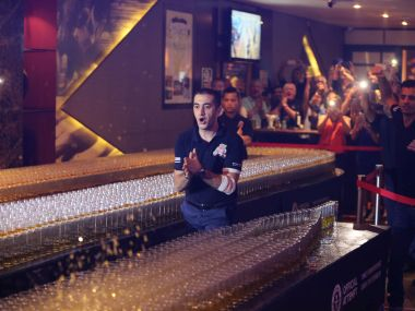 Ahmad Taher, food and beverage manager for Citymax Hotels in Dubai, pushes over a shot glass in a successful attempt at the world's longest domino drop shot. AP