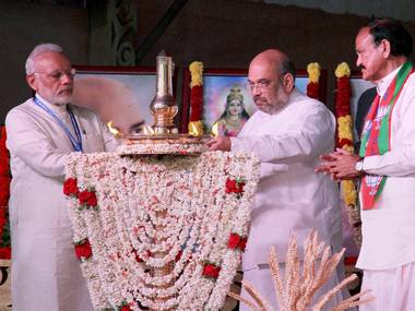 PM Modi with BJP President Amit Shah lights the lamp as Union Minister Venkaiah Naidu looks on during BJP's National Council Meeting in Kozhikode . PTI