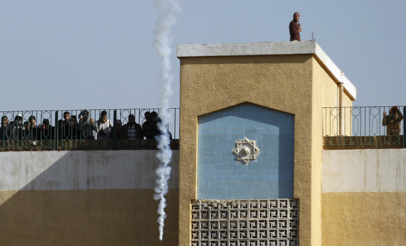 A file image of students of Al-Azhar University, supporters of the Muslim Brotherhood and deposed President Mohamed Mursi, look on from the top of a building at tear gas fired by riot police, at the university's campus in Cairo. Reuters