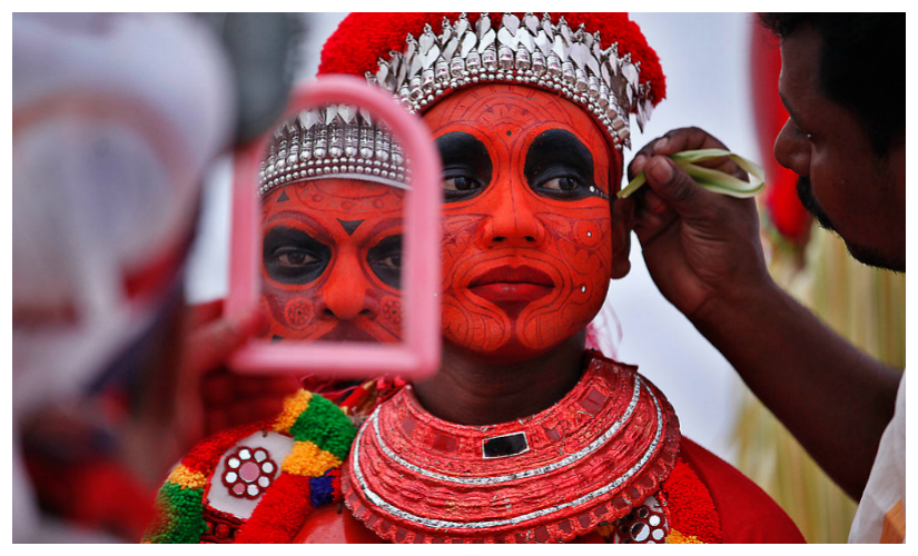 A Theyyam dancer prepares for a dance recital during Onam celebrations in Kerala. Getty Images