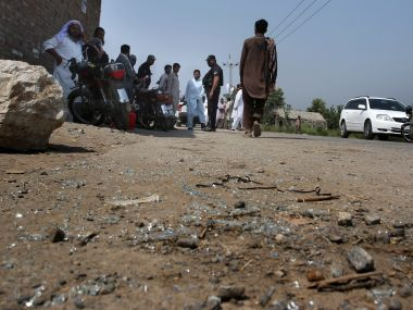 Pakistani police officers and local residents gather at the site of firing incident at Garhi Sohbat Khan on the outskirts of Peshawar. AP