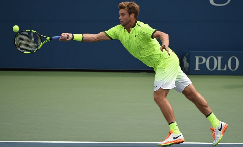 Ryan Harrison of the US returns to Milos Raonic of Canada. AFP