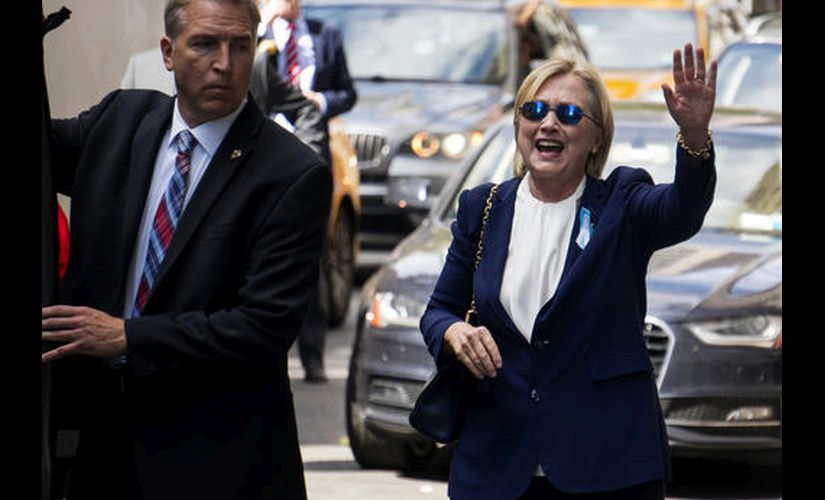 Democratic presidential candidate Hillary Clinton waves as she walks from her daughter's apartment building on Sunday. AP