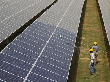 Workers clean photovoltaic panels inside a solar power plant in Gujarat. Reuters