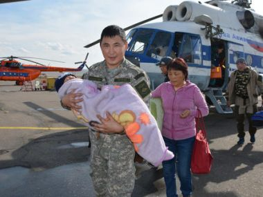 A soldier carries the 3-year-old boy rescued after going missing  in Siberian forest. AP