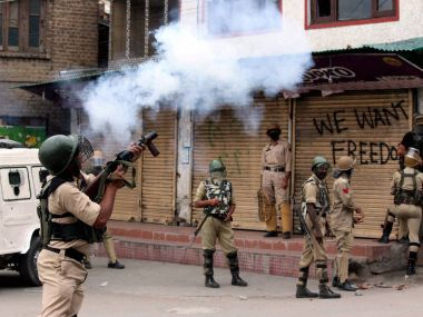 Security jawans fire tear gas shells to disperse protesters who staged a protest march towards Lal Chowk in Srinagar. PTI