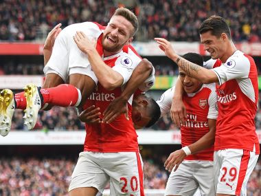 Ten-man Arsenal edged Swansea City to move joint top of the Premier League. AFP
