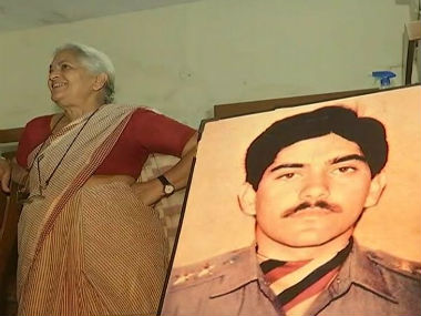 Nirmala Devi Sharma stands alongside the picture of her martyred son Captain Devashish Sharma. News18