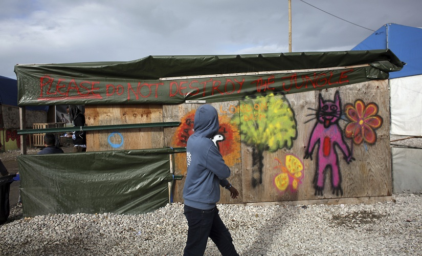 """A migrant walks past a restaurant where a banner reads """"Please do not destroy the jungle"""" in a makeshift migrant camp near Calais, France, Saturday, Oct. 22, 2016. French authorities say the closure of the slum-like camp in Calais will start on Monday and will last approximatively a week in what they describe as a """"humanitarian"""" operation. (AP Photo/Thibault Camus)"""