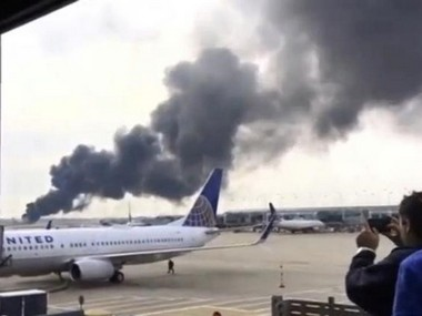 Smoke rises after an American Airlines jet (background) that caught fire at O'Hare International Airport in Chicago on 28 October. Reuters