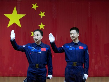 Chinese astronauts Jing Haipeng (L) and Chen Dong wave at a news conference before China launches the Shenzhou 11 manned spacecraft, in Jiuquan, China on 16 October 2016. Reuters