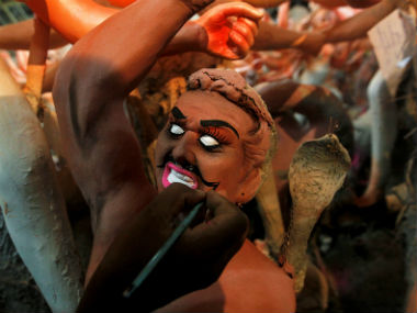 An artisan paints an idol of mythological demon Mahisasura ahead of the Durga Puja festival. Reuters