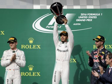 Lewis Hamilton, center, celebrates his win as second-place Nico Rosberg, left, and third-place Red Bull driver Daniel Ricciardo look on. AP
