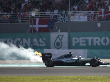 Flames and smoke pour from the rear of Mercedes driver Lewis Hamilton's car. AP