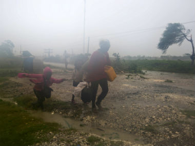 Family rushes to safety after hurricane Matthew hits Haiti. AP