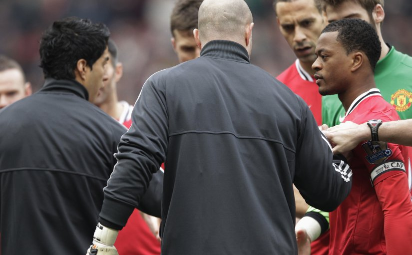 Manchester United's Patrice Evra reacts after Liverpool's Luis Suarez ignored his handshake before their Premier League match. Reuters