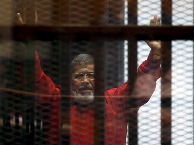 FILE PHOTO: Deposed President Mohammad Morsi greets his lawyers and people from behind bars at a court during his court appearance with Muslim Brotherhood members on the outskirts of Cairo, Egypt. Reuters