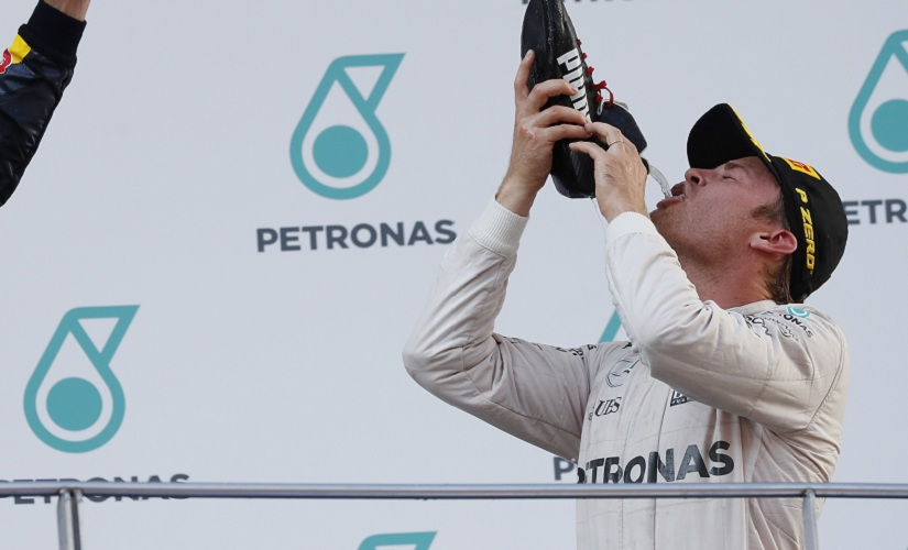 Mercedes driver Nico Rosberg drinks champagne from his shoe after finishing third. AP