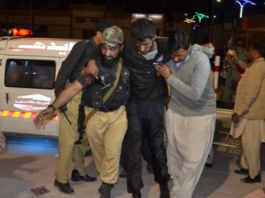 A Pakistani volunteer and a police officer rush an injured person to a hospital in Quetta. AP