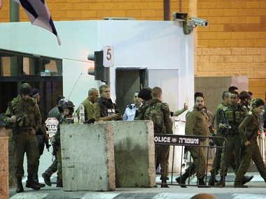 Israeli army soldiers deploy at the site of the attack by a Palestinian man who was shot and killed by Israeli police after he attacked a security officer at the Israeli Qalandia checkpoint, near Jerusalem, late Friday, Sept. 30, 2016. Israeli security forces shot and killed a Palestinian man who pulled out a knife and stabbed a security officer seriously wounding him in the West Bank, Israeli police said. (AP Photo/Mahmoud Illean)