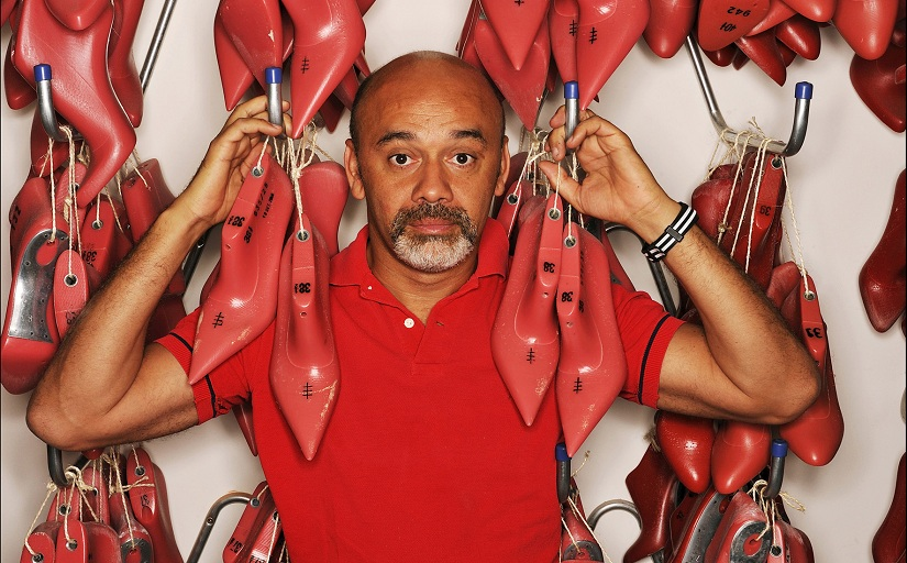 Louboutin holding up his signature red soled shoe. Image courtesy: Christian Louboutin by Mathieu Cesar.