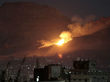 Smoke and fire rises from a building hit in the airstrikes. AP