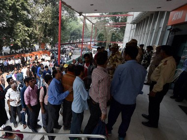 A file image of people queuing outside a bank. PTI
