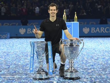 Andy Murray celebrates winning the final against Novak Djokovic with the ATP World Tour Finals trophy and Year-End No. 1 Trophy. Reuters