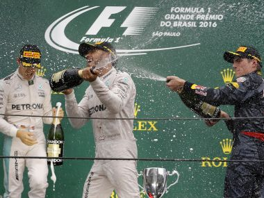 Race winning driver Lewis Hamilton is sprayed with champagne by third placed finisher Max Verstappen. Reuters
